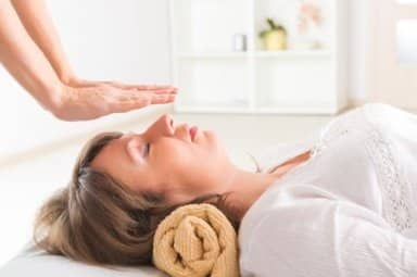 Professional Reiki healer doing reiki treatment to young woman